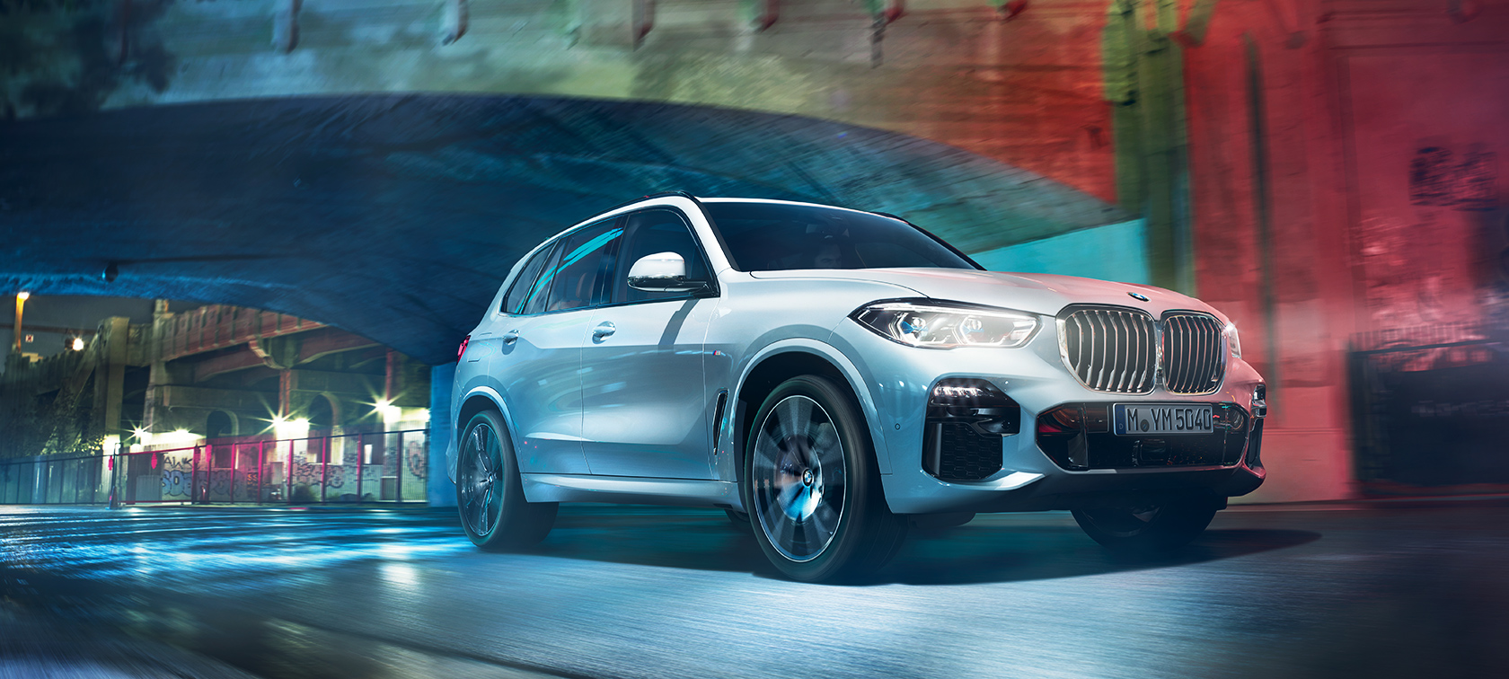 Driving shot of the BMW X5 at night in an urban setting